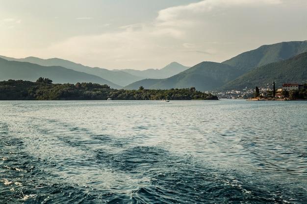 山の景色を望む海の明るい太陽。モンテネグロのアドリア海。観光と旅行。テキストのためのスペース。