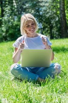 な若いブロンドの女性の笑顔は、夏の晴れた日にラップトップを持つ公園の芝生の上に座っています。