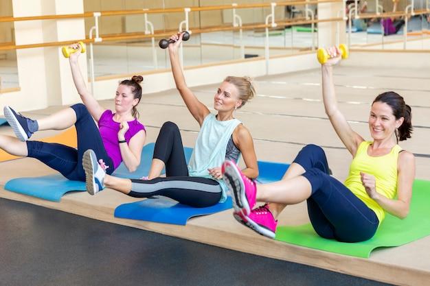 Женщины делают упражнения с гантелями на групповых тренировках в тренажерном зале