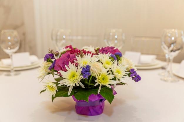 テーブルの上の花の美しい花束。宴会のお祝いデコレーション。テキストのためのスペース。