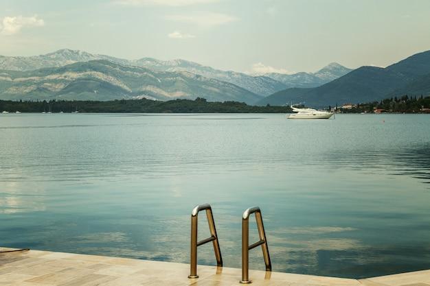 海の白いモーターヨット桟橋から美しい山々の景色