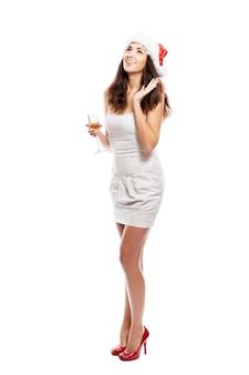 Смеется красивая молодая женщина в шляпе санта-клауса и с бокалом шампанского в руке. полный рост. вертикальная. изолированный над белизной.