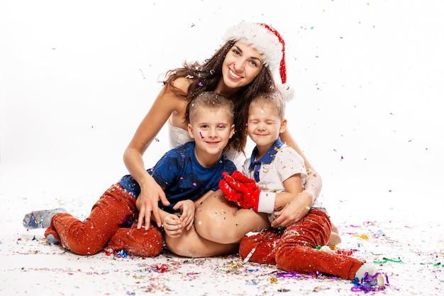 Красивая молодая женщина с детьми в шляпе санта-клауса смеется. счастливая семья празднует новый год. белый