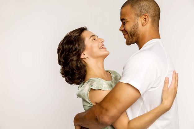 Любящая молодая пара, разные расы, обнимаются и смеются