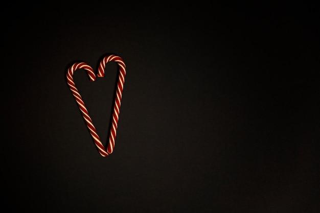 ハート形の黒い背景にクリスマスキャンディー。テキスト用のスペース。
