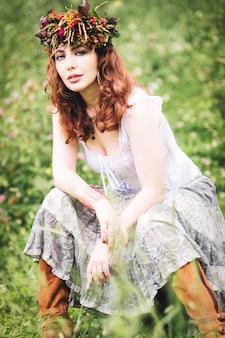 Красивая рыжеволосая девушка в поле в одежде в стиле богемного