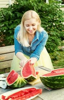 Красивая девушка режет арбуз в саду
