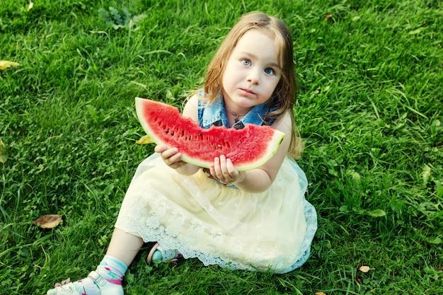 庭でスイカを食べる少女