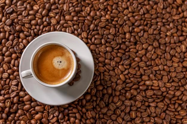 Маленькая белая чашка кофе стоит на кофейных зерен. ароматное удовольствие.