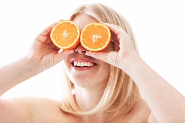 Счастливая молодая женщина без одежды с апельсинами разрезать пополам на глазах. здоровый образ жизни. крупный план.