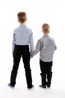 青いシャツの弟が手をつないで立っています。背面図