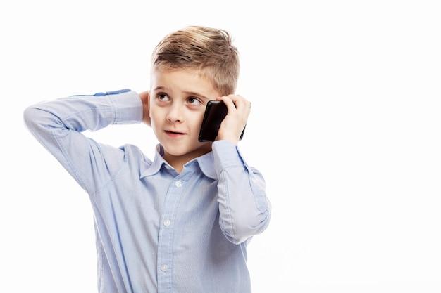 電話で話している青いシャツを着たかわいい少年少年。閉じる。