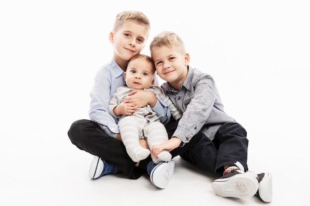 Два брата держат новорожденного и улыбаются. любовь и нежность в семье.