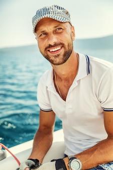 海でヨットの上で若い男