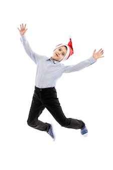Улыбаясь прыжки школьника в шапке санта-клауса. полный рост. новогоднее настроение изолированные на белом фоне. вертикальная.