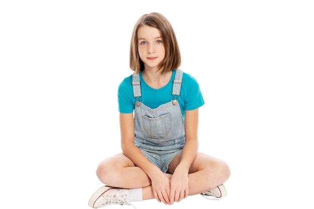 座っているかわいい十代の少女。白い背景に分離しました。