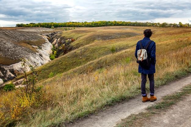 色とりどりの草で美しい秋のキャリアの若い男。ゴージャスな風景。