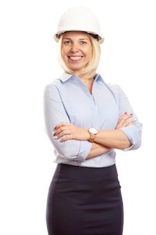 Улыбается молодая женщина в офисе одежду и строительство шлем на голове. вертикальный
