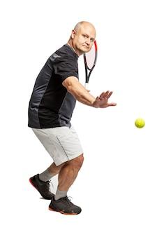 中年のハゲ男がテニスをしています。左利き。白い背景に分離