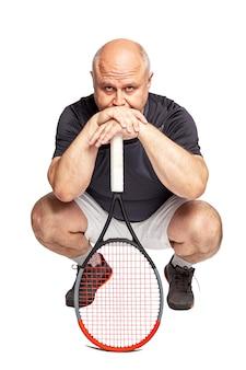 Лысый мужчина средних лет с теннисной ракеткой приседает. отдельный на белом фоне