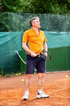 Мужчина средних лет играет в теннис на корте с естественной земной поверхностью в солнечный летний день.