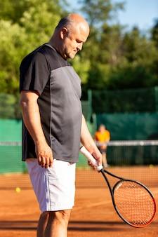 Лысый мужчина средних лет играет в теннис на открытом корте. солнечный день