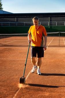 男は試合のためにコートを準備します。滑らかなラインマーキング。晴れた夏の日