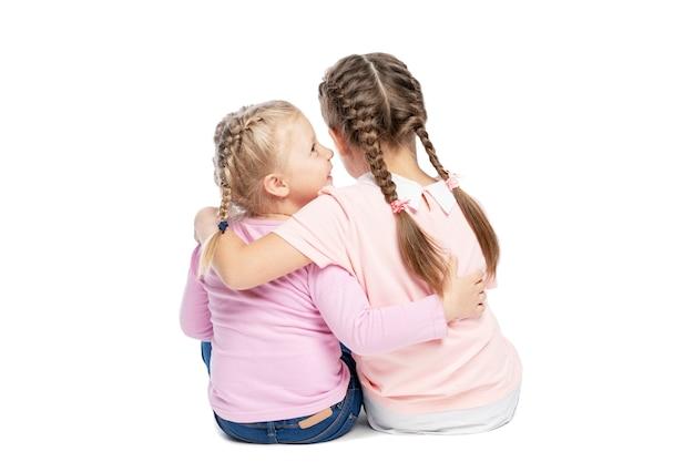 Подруги в розовых свитерах и джинсах обнимаются и смеются. вид сзади. изолированные на белом фоне.