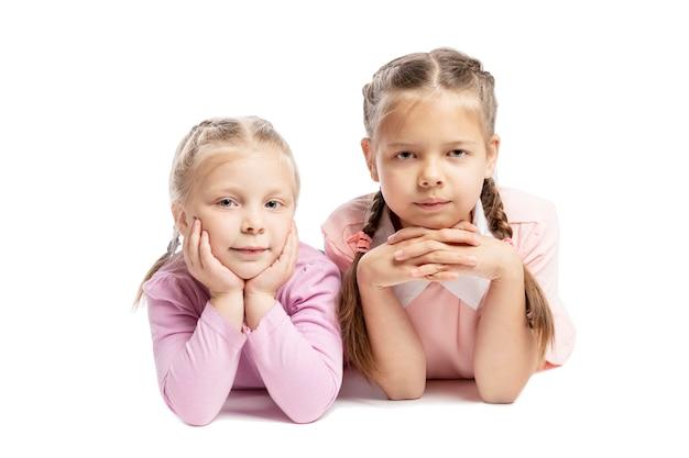 ピンクのセーターのガールフレンドは横になっていると笑みを浮かべています。小さなお子様。白い背景に分離されました。