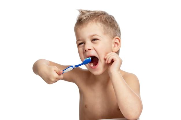 小さな男の子は積極的に歯を磨いています。白い背景に分離されました。