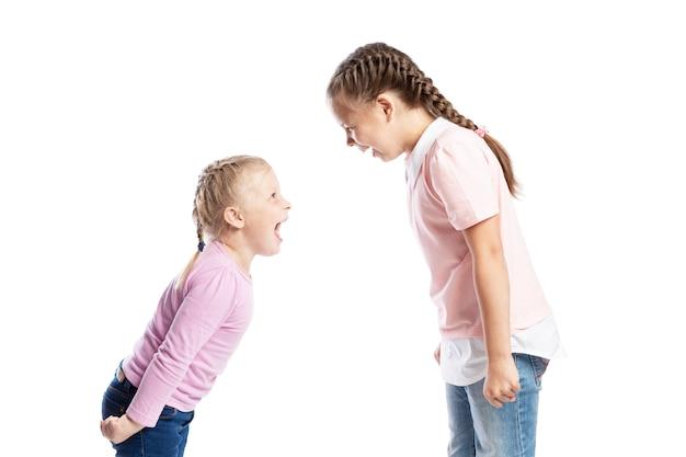 小さな子供たち、ピンクのセーターを着たガールフレンドとジーンズはお互いに叫びます。怒りとストレス。白い背景に分離されました。