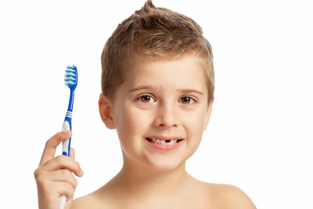 少年は積極的に歯を磨いています。白い背景に分離されました。
