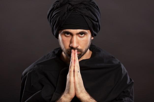 Молодой человек в тюрбане молится, сложив руки перед петицией. черный фон.