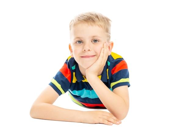 明るいストライプのセーターを着た男子生徒が床に横になって笑っています。白い背景に分離されました。