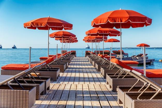 ファッショナブルなリゾートにあるオレンジ色のマットレスとパラソル付きのデッキチェアの列。