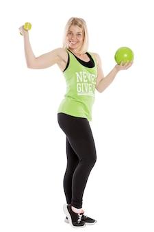 Молодая усмехаясь женщина в спортивной одежде с гантелью. занятия аэробикой. изолированные на белом фоне