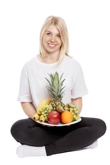 笑顔の若い女性がフルーツプレートを手に座っています。白い背景に分離