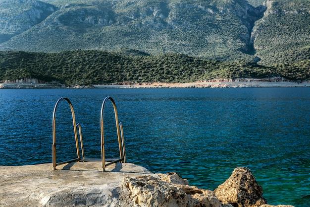 Лестница к морю в красивой лагуне. волшебный вид на море и горы. успокойся и расслабься.