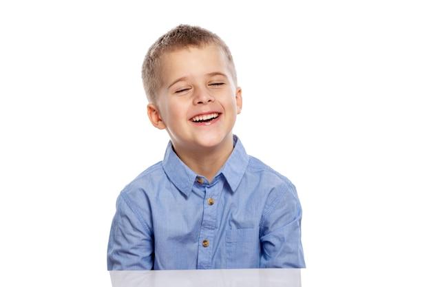 Милый мальчик школьного возраста сидит за столом и смеется. отдельный на белом фоне.