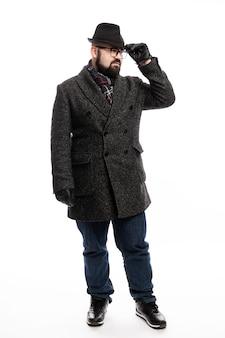 コートと帽子のひげを持つエレガントな男。彼は白い壁で完全に成長し、帽子を握りしめています。垂直。