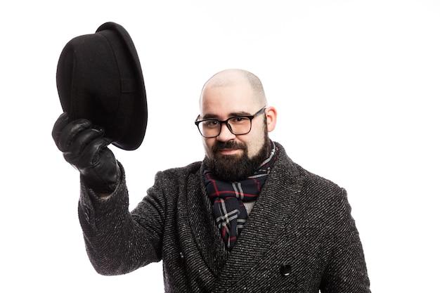 コートのひげを持つエレガントな男。彼は帽子を脱いだ。白い壁に分離されました。