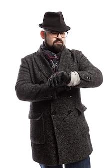 コートと帽子のひげを持つエレガントな男は彼の時計を見てください。白い壁。垂直。