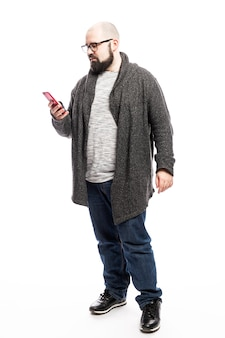 Лысый мужчина в очках с телефоном в руках. полный рост. изолированный над белой стеной. вертикальная.
