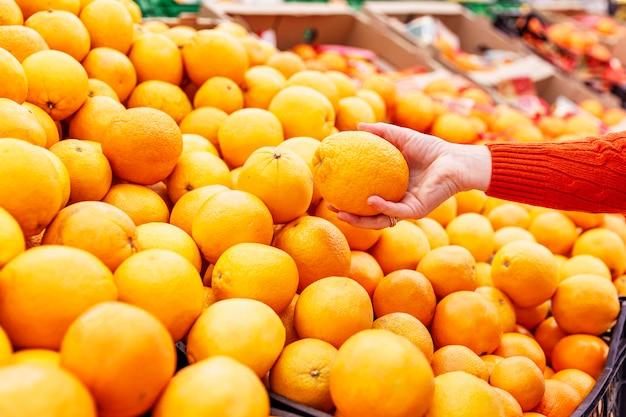 スーパーマーケットのカウンターでジューシーな黄色オレンジ。女性は果物を選びます。