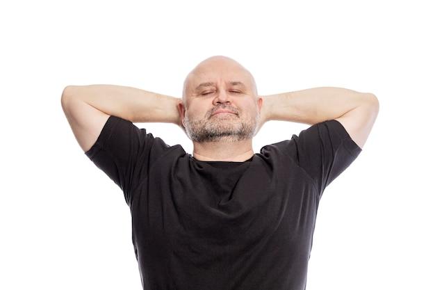 Лысый мужчина средних лет в черной футболке, руки за голову, улыбается. изолированный над белизной.