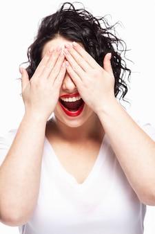 若い女の子は、彼女の手で目を閉じて笑います。白い壁。閉じる。