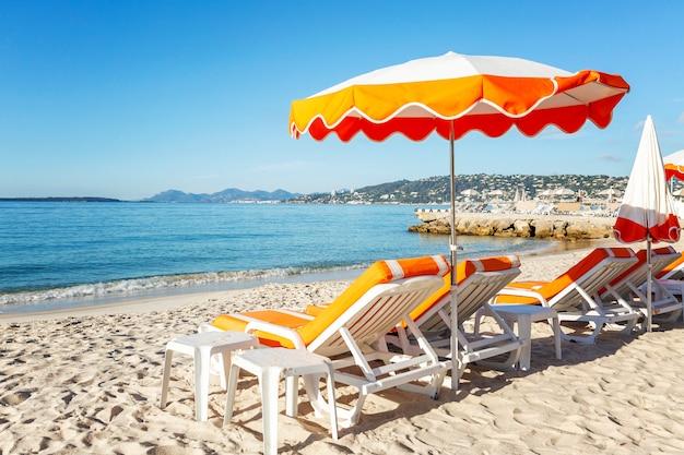 Шезлонги с оранжевыми матрасами на песчаном пляже на стене спокойного синего моря. идиллия и отдых. пространство для текста.