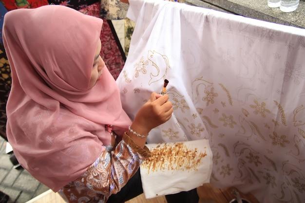 スラバヤで女性が伝統的な傾斜を使ってバティックを作るのに忙しい