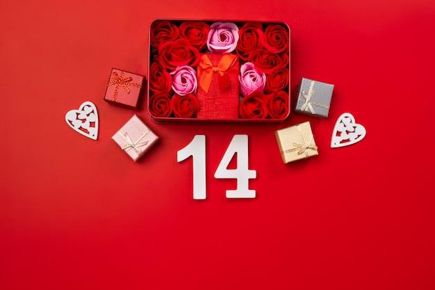 豪華なギフトボックスとバレンタインデーのための赤い背景に白い木製の愛の手紙で美しい赤いバラのトップビューボックス。