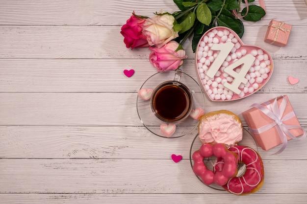 День святого валентина. романтический утренний мотив, чай, роза и сладкие пончики.